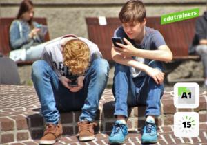 2 tieners buiten op de stoep met gsm