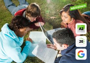 4 tieners liggend in het gras leren op de computer